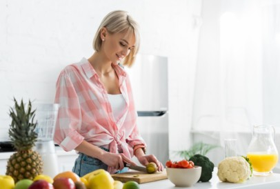 happy blonde woman cutting kiwi fruit near ingredients in kitchen